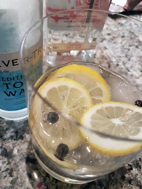 Gin & Tonic mit Zitrone und Wacholderbeeren.